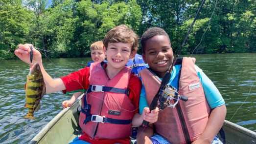 Two boys in a boat on the lake holding up the fish they caught
