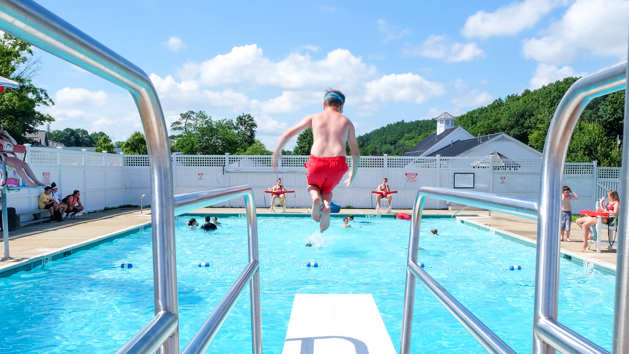 Boy jumping off of a diving board into the pool