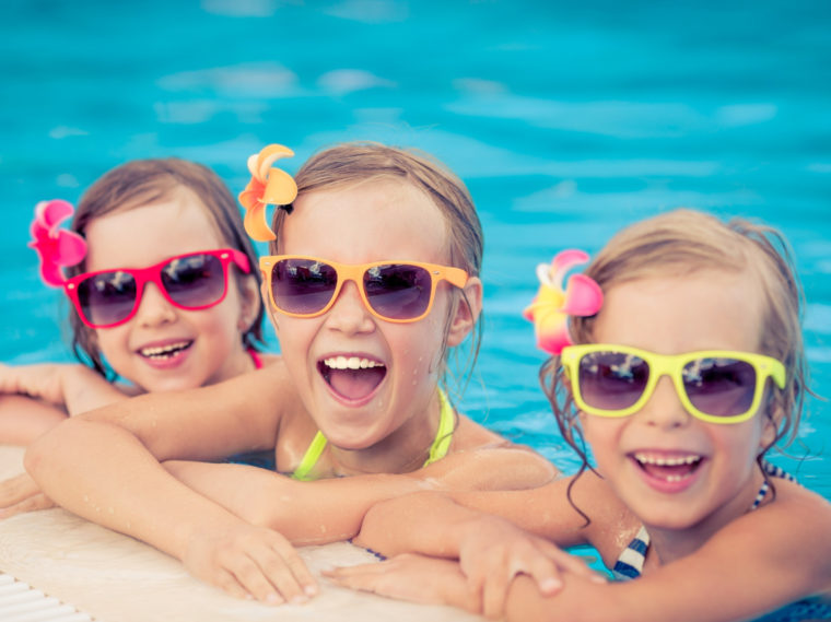 Three girls with sunglasses in the pool smiling
