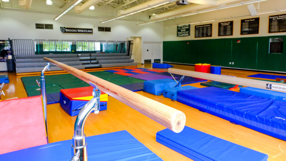 The indoor gymnasium with balance beam and mats