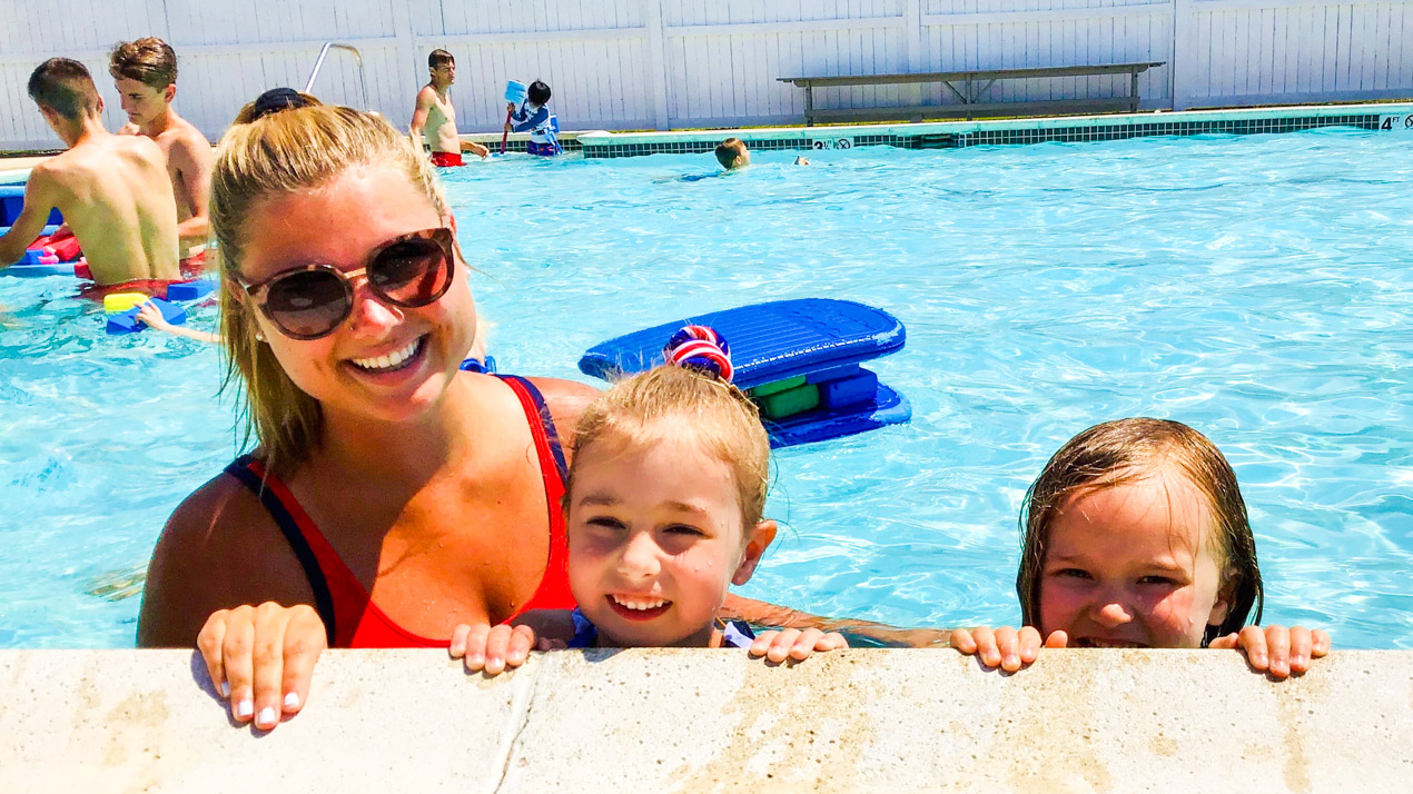 Female lifeguard with two girl campers in the pool