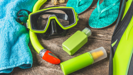 Flat lay of snorkel mask and tube next to flip flops and sunscreen