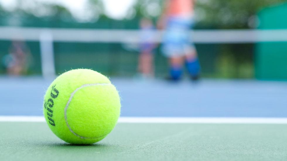 Up close photo of a tennis ball on a tennis court
