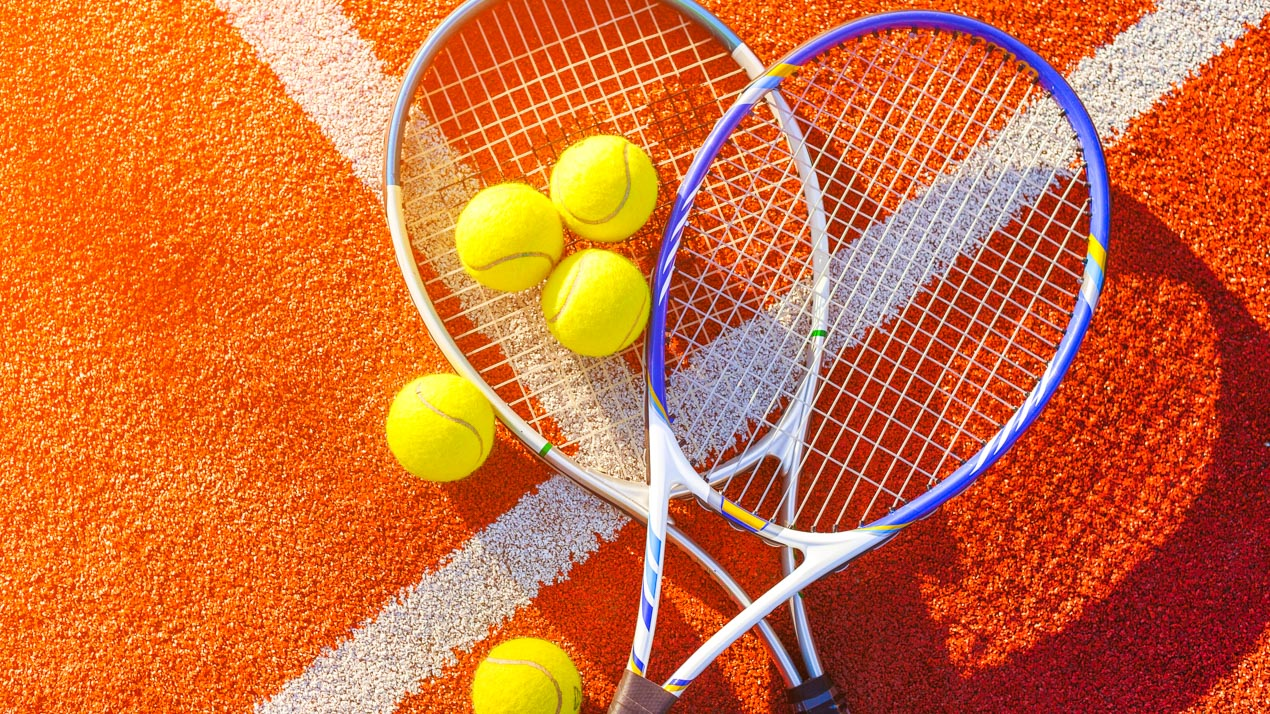 Flat lay of two tennis rackets and tennis balls on a clay tennis court