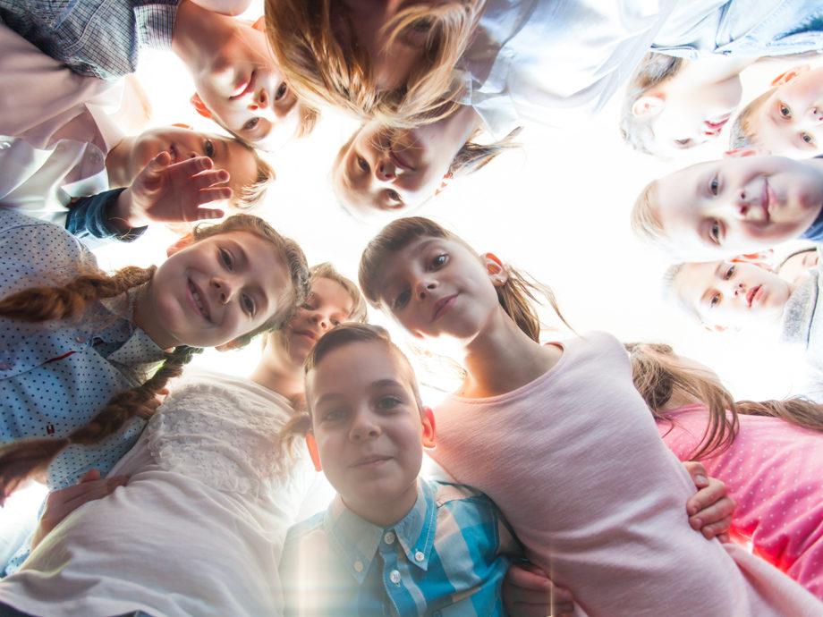 Kids gathered in a circle looking down at the camera facing up