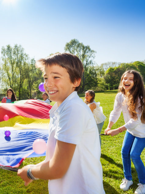 Kids having fun outside with a parachute
