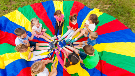 Group of kids sitting in a circle on top of a parachute