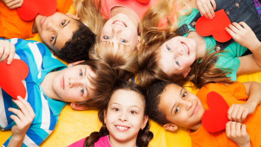 Group of kids laying in a circle with their heads in the center