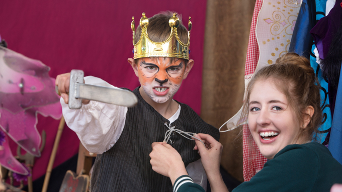 Boy in a crown and tiger face paint getting his costume adjusted by a staff member